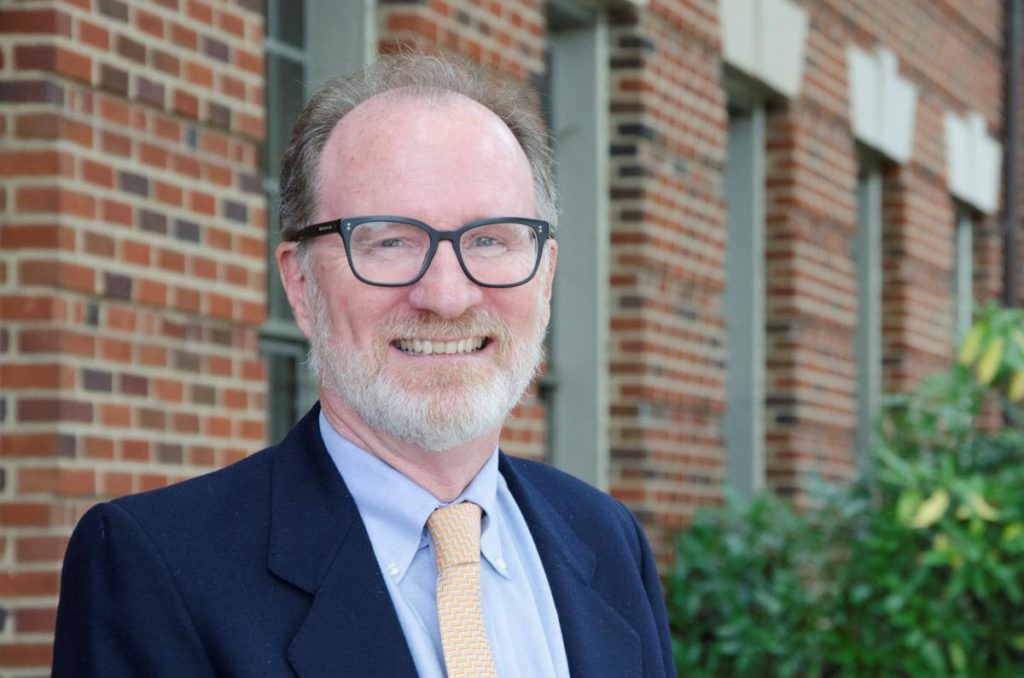 Dr. Crooke, Senior Associate Dean of Faculty and Academic Affairs, smiling in front of the Medical-Dental Building.